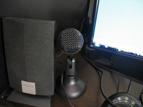 Microfone dinâmico para PC da AOVES, ao lado da caixa de som e do monitor
