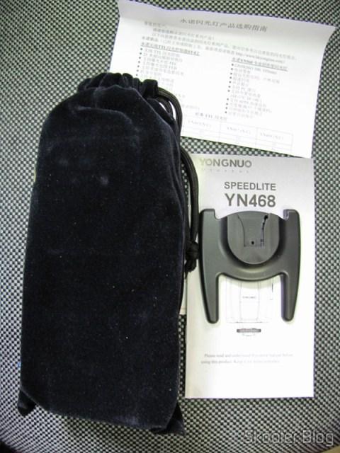 O Flash Yongnuo Speedlite YN-468 em sua bolsa, o manual de instruções e a base