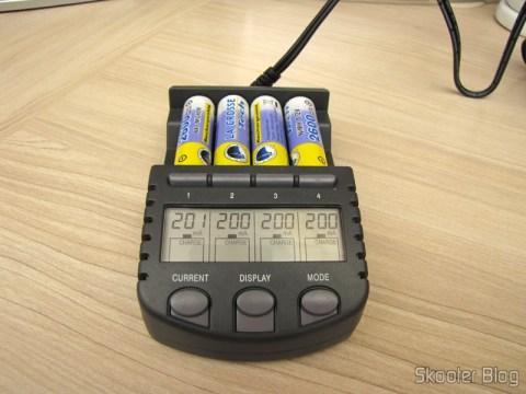 Carregador de Pilhas La Crosse Technoly Alpha Power BC1000 (La Crosse Technology Alpha Power Battery Charger, BC1000) em funcionamento fazendo teste das pilhas AA, display LCD mostrando a corrente atual em cada uma delas