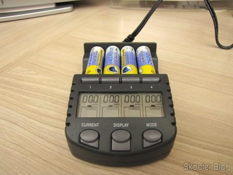 Carregador de Pilhas La Crosse Technoly Alpha Power BC1000 (La Crosse Technology Alpha Power Battery Charger, BC1000) em funcionamento fazendo teste das pilhas AA, mostrando a carga que cada uma delas já recebeu