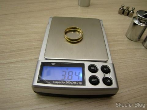Testando a balança de precisão com uma aliança de ouro