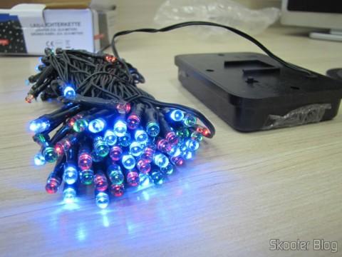 Pisca-Pisca com 100 Lâmpadas LED RGB (vermelhas, verdes, e azuis), 2 Modos, Alimentado por Energia Solar, cabo de 12 metros (Solar Powered 2-Mode 100-RGB LED Decoration Light Strip - Deep Green (12m-Cable)), em funcionamentoPisca-Pisca com 100 Lâmpadas LED RGB (vermelhas, verdes, e azuis), 2 Modos, Alimentado por Energia Solar, cabo de 12 metros (Solar Powered 2-Mode 100-RGB LED Decoration Light Strip - Deep Green (12m-Cable)), em funcionamento