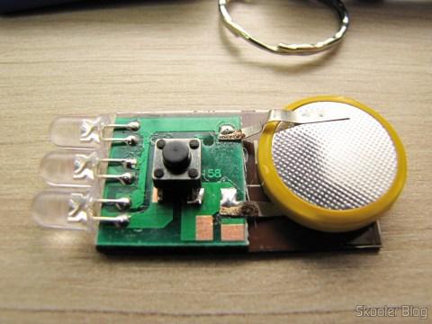 Um dos Chaveiros Lanternas com 3 LEDs Auto Recarregáveis com Energia Solar visto por dentro: FALSO!