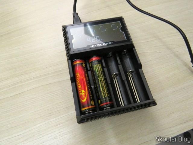 Carregador de Baterias Nitecore Digicharger D4EU, em funcionamento com baterias 18650.