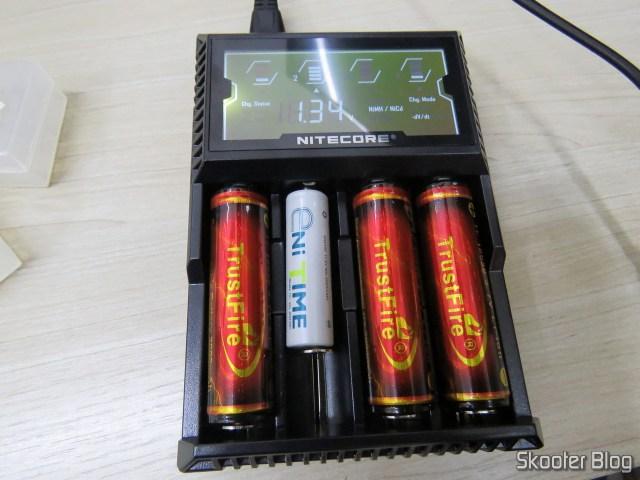 Carregador de Baterias Nitecore Digicharger D4EU, em funcionamento com baterias 18650 e NiMH.