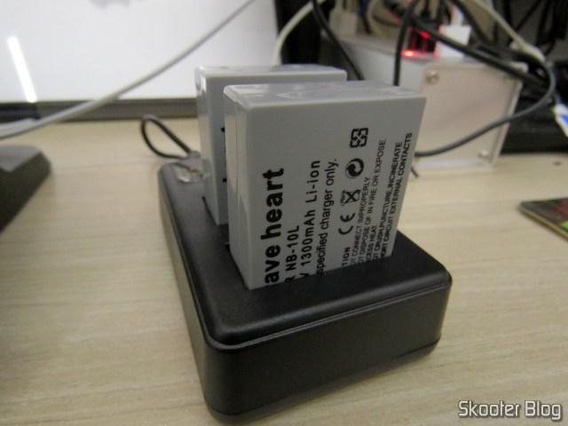2 Baterias NB-10L para câmera Canon no Carregador USB com LCD, em funcionamento.