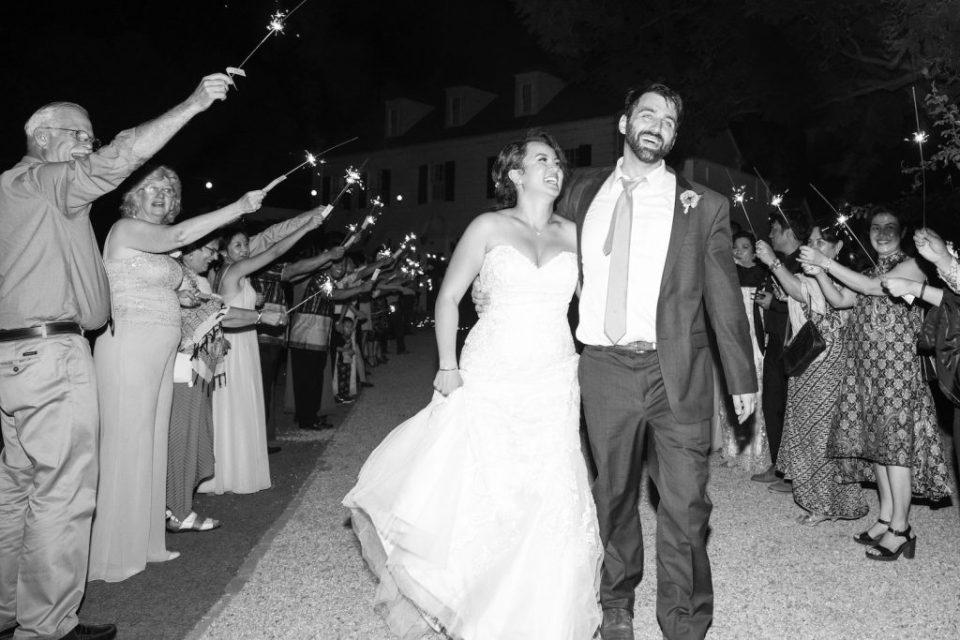 bride and groom smile during sparkler exit