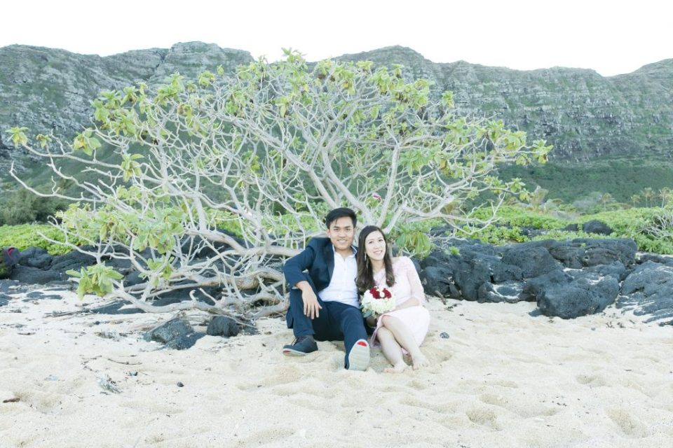 couple sit in sand