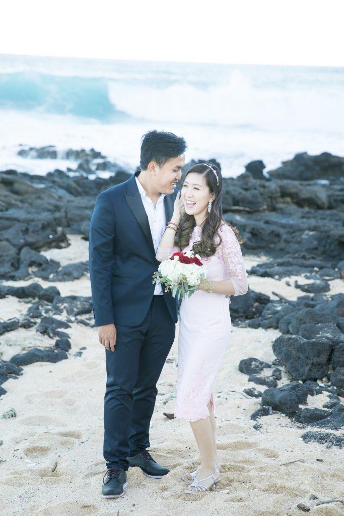 couple laugh as wave crashes