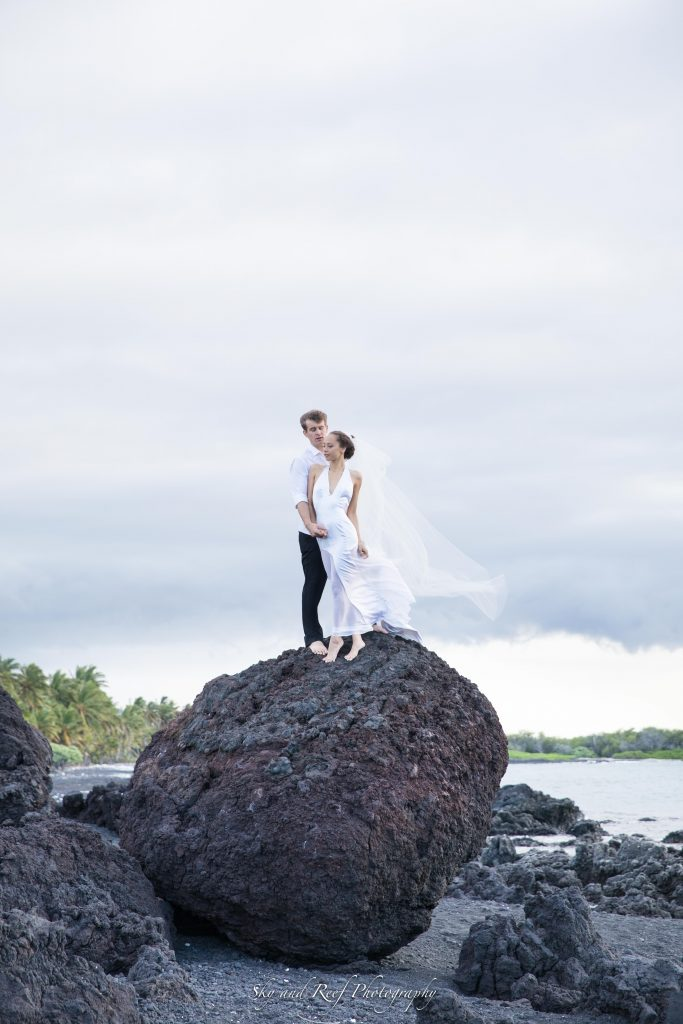 bride and groom climb on rock
