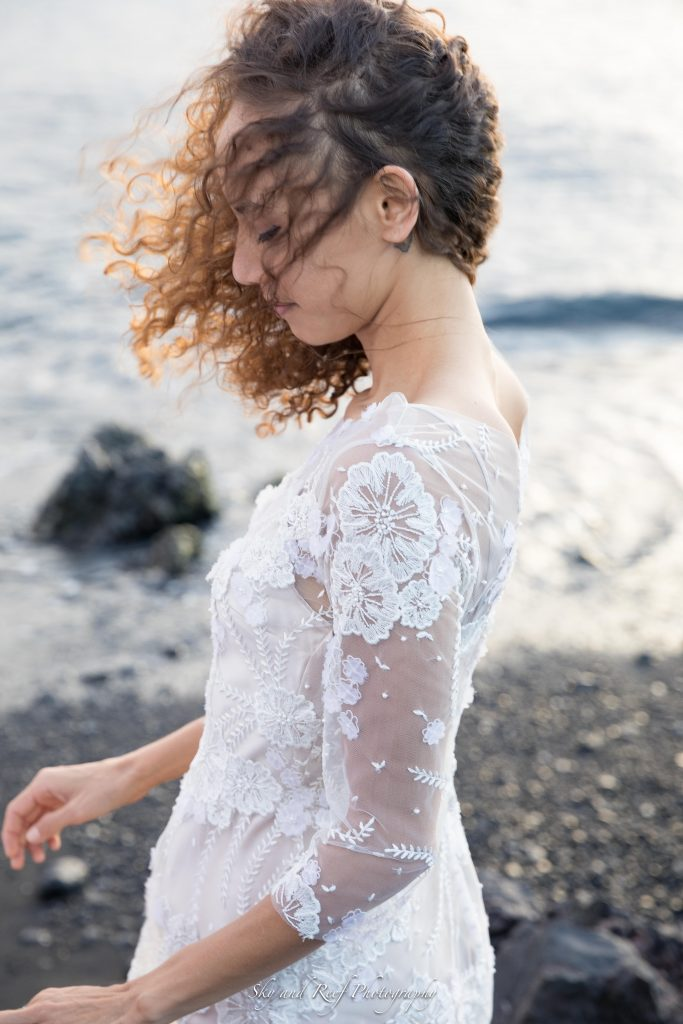 bride in wind Waikoloa, Hawaii with lace wedding dress