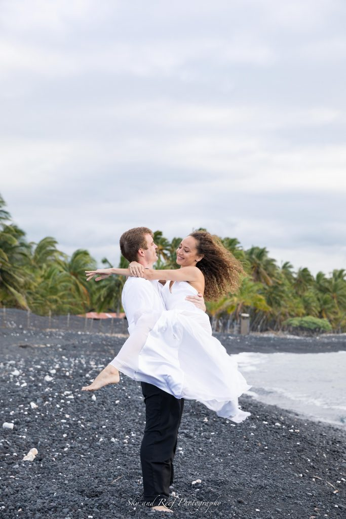 groom picks up bride and spins her around on black sand beach in wedding dress