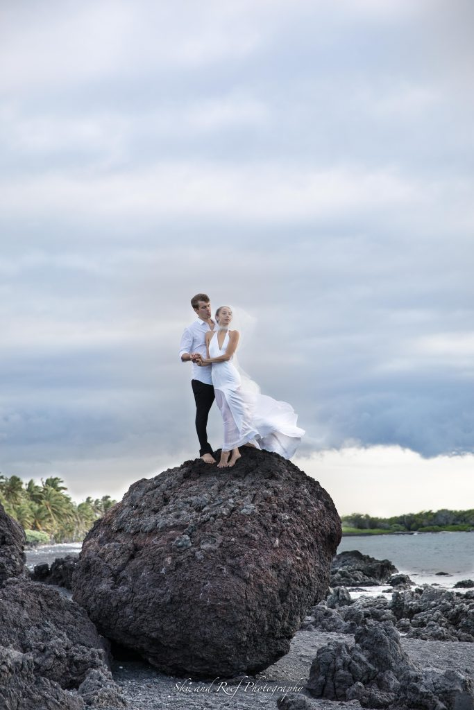 bride wears viel in wind on lava rock