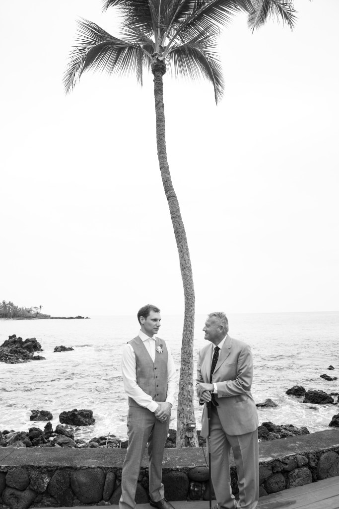 groom and father of bride talk after wedding under palm tree