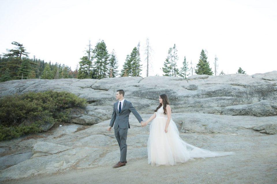 groom leads the way on the rocks yosemite wedding