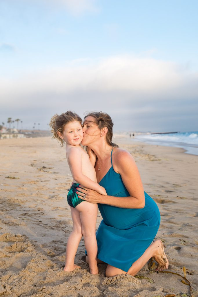 mom kisses toddler on beach while pregnant