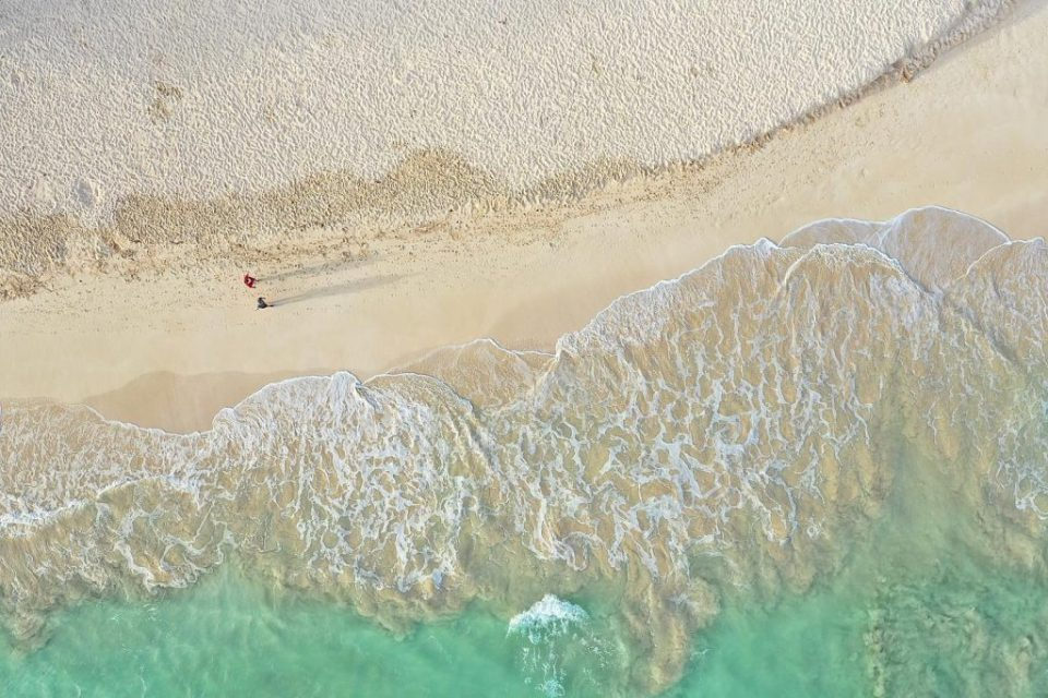 couple walking on the beach drone shot