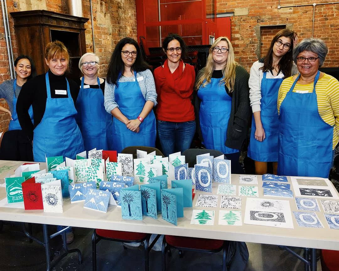 A group of people holding up their lino prints from one of Jenna's workshops
