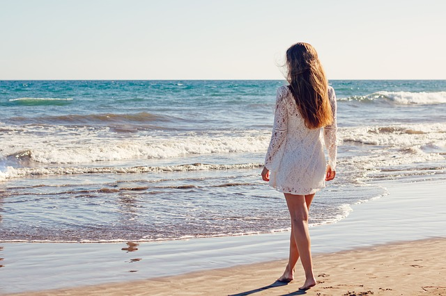 image: woman in beautiful sun dress stands on beach look out at ocean
