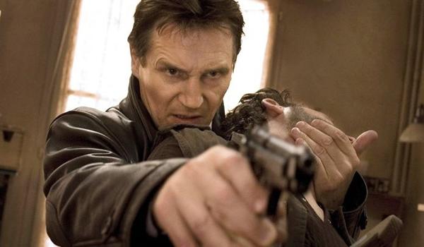 Liam Neeson liquidando a un tipo con una mano mientras encañona a otro con una pistola.
