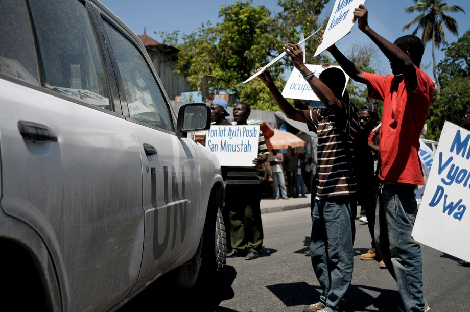 Demonstrators holding placards surround a U.N. vehicle during a protest in Port-au-Prince, July 28, 2011. Protesters said they want justice from the United Nations Stabilization Mission in Haiti (MINUSTAH) after a study by the U.S. Centers for Disease Control and Prevention (CDC) showed that a unit from Nepal might be responsible for bringing cholera into the country, which has killed more than 5,500 people so far.