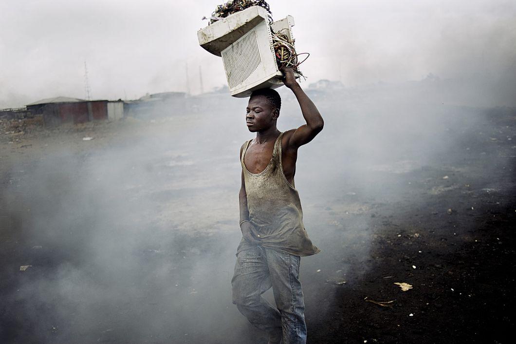 «Sur cette photo prise à Accra, auGhana, un jeune homme transporte des câbles dans un vieil écran d'ordinateur. Les conditions climatiques défavorables empêchent la fumée de se dissoudredans l'atmosphère. Elle flotte dans l'air, à la manièred'un brouillard. On ne peut pas y voir à plus de 2 mètres. La décharge est divisée en deux.D'un côté, des garçons brûlent les câblespour récupérer le cuivre. De l'autre, on trouve de petites cahutes en bois dans lesquelles sont démontés les appareils pour récolter des composants.»
