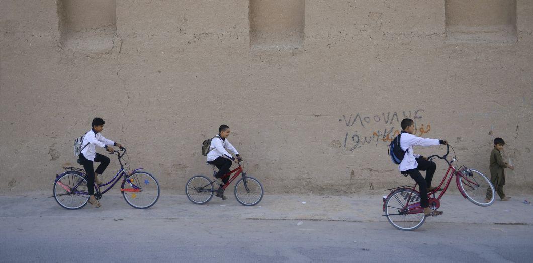 Des écoliers à vélo dansla banlieue de Herat, au sud de l'Afghanistan.| Hoshang Hashimi/ AFP