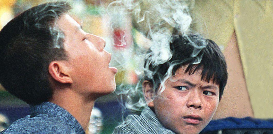 Un enfant souffle la fumée d'une cigarette, à Beijing, en Chine, en 1998 |Chai Hin Goh / AFP