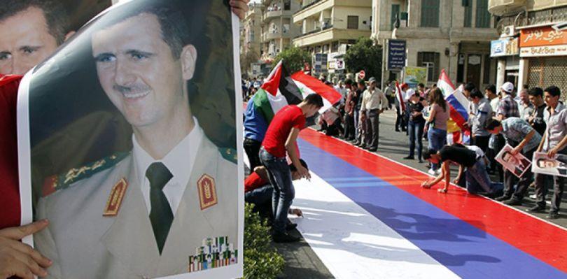 Des partisans de Bashar el-Assad signent un drapeau russe lors d'un rassemblement à Damas, le 12 octobre 2011. REUTERS/ Khaled al-Hariri.