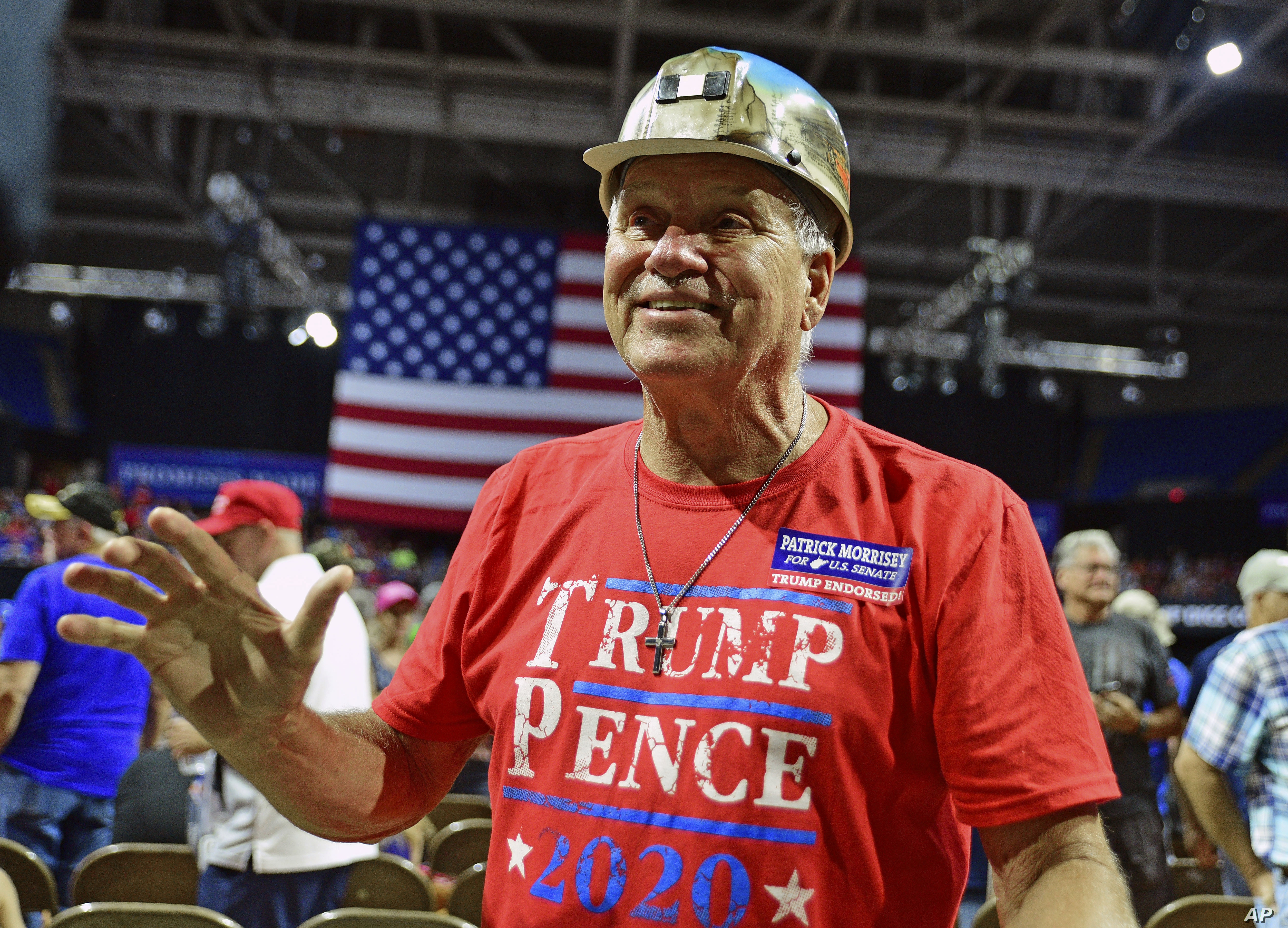 Trump supporter John Berta, of Oceana, W.Va., a retired coal miner, waves to the crowd at a rally with President Donald Trump, Tuesday, Aug. 21, 2018 at the Civic Center in Charleston W.Va. (AP Photo/Tyler Evert)