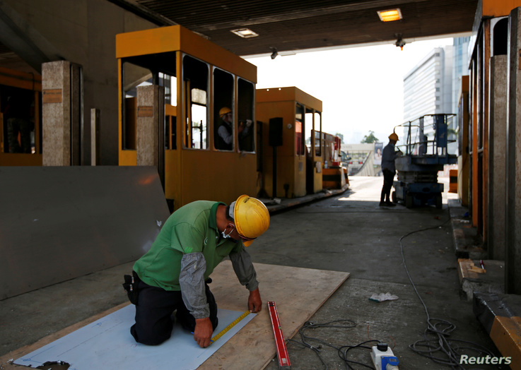 A worker repairs toll booths which were damaged during protests, at the Cross Harbour Tunnel near Hong Kong Polytechnic…
