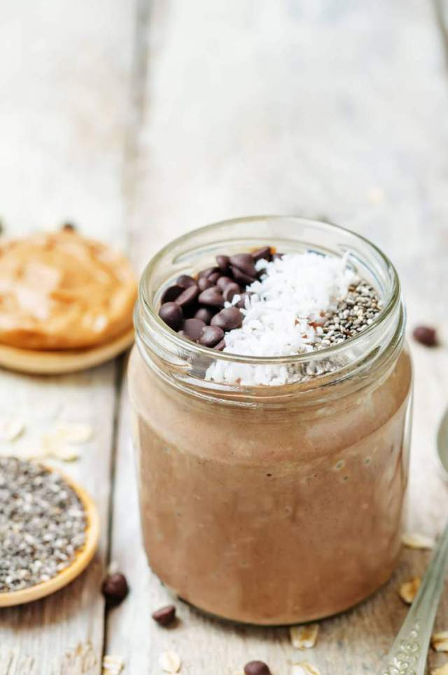 Chocolate chia seed pudding in a glass jar with peanut butter and chia seeds in the background.