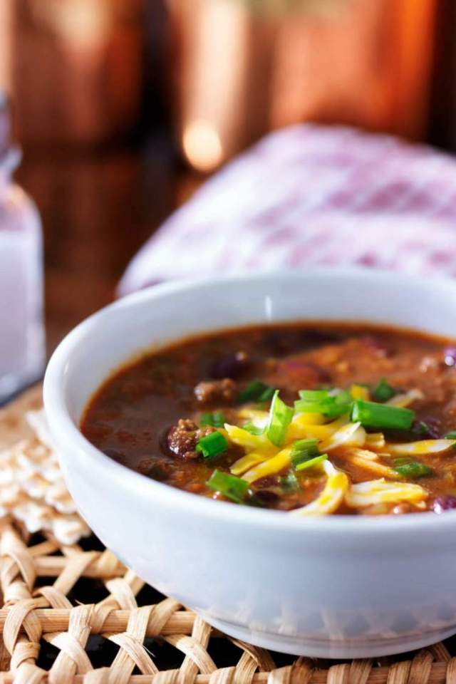 Beef chili in a white bowl with a glass blurred in the background.