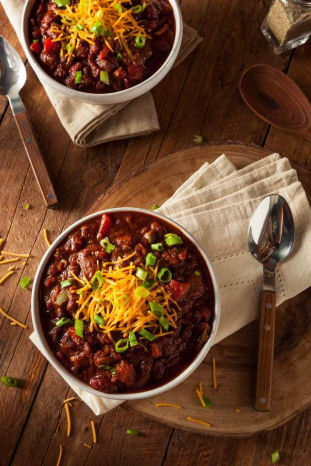 Low Carb Beef Chili in a ceramic bowl with cheese and green onion.
