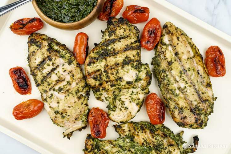 Healthy Pesto grilled chicken on a baking sheet next to a bowl of homemade pesto.