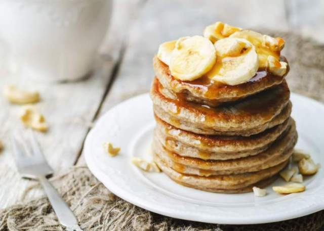 Protein banana pancakes on a plate with maple syrup.