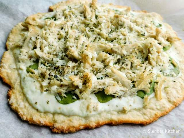 Weight Watchers Chicken Alfredo Pizza on parchment paper with spinach and cheese.
