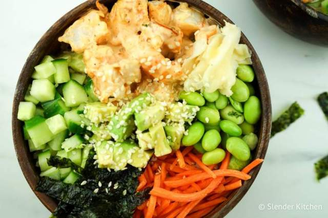 Spicy Shrimp Sushi Bowls in a wooden dish with sesame seeds and seaweed.