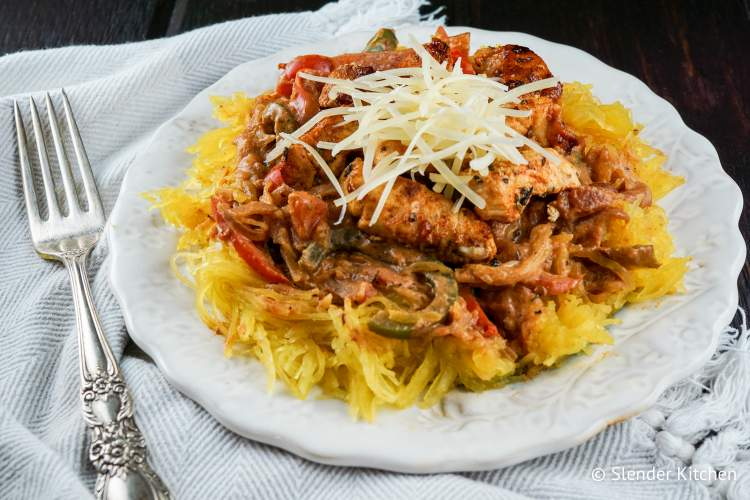 Creamy Cajun chicken over spaghetti squash on plate with fork.