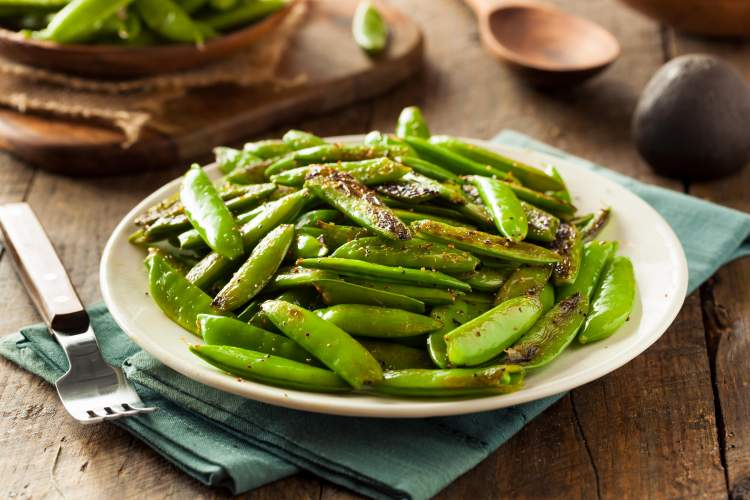 Garlic sugar snap peas on a plate on a wooden table.