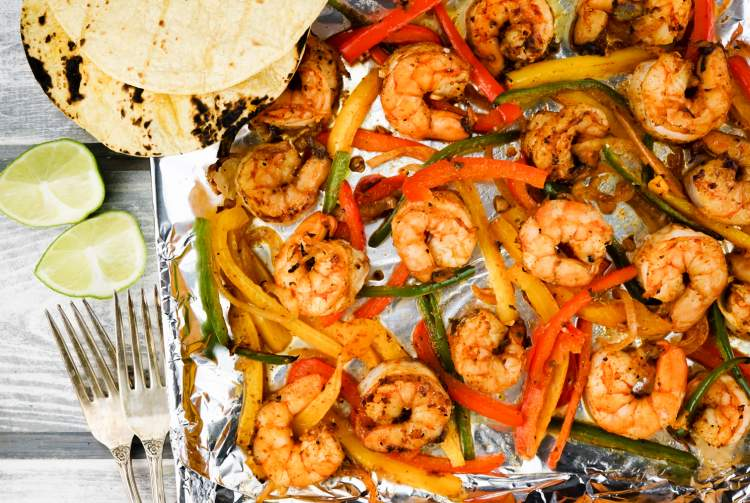 A sheet pan with shrimp, peppers, and onions
