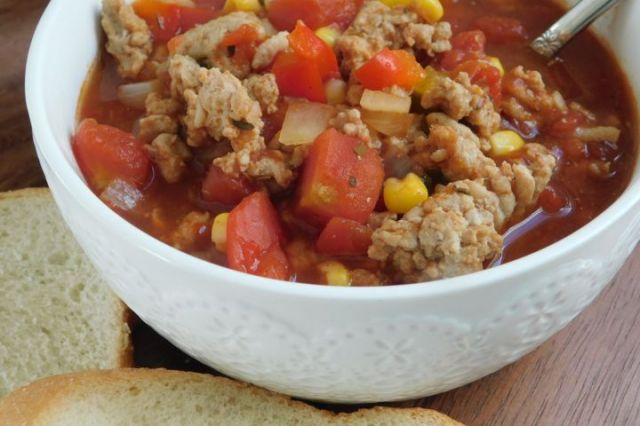 Weight Watchers chili with ground chicken, tomatoes, corn, and spices in the slow cooker.