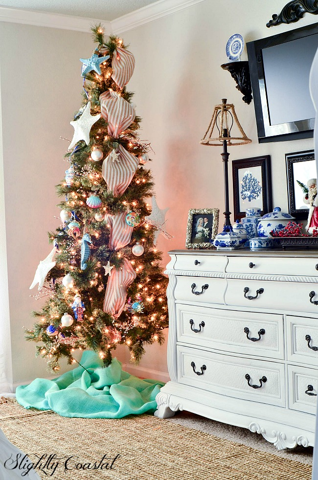 A Coastal Christmas tree in a decked out for master bedroom with Christmas decor.