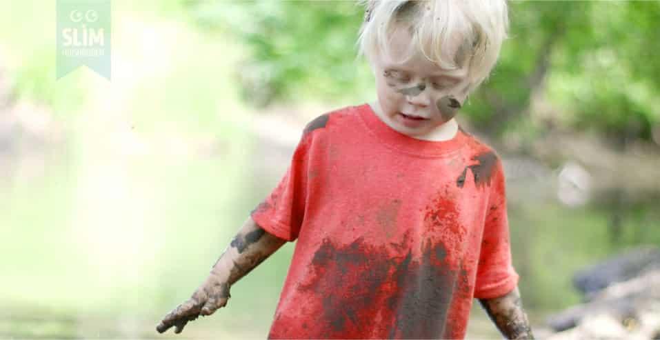 Kind met moddervlekken en aardevlekken