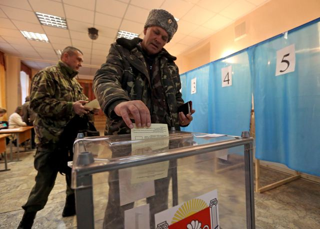 A Cossak casts his ballot during the referendum on the status of Ukraine's Crimea region at a polling station in Simferopol March 16, 2014. Voting got underway in Crimea on Sunday in a referendum that will decide whether the Black Sea peninsula leaves Ukraine and becomes part of Russia. REUTERS/Sergei Karpukhin (UKRAINE  - Tags: POLITICS CIVIL UNREST ELECTIONS)