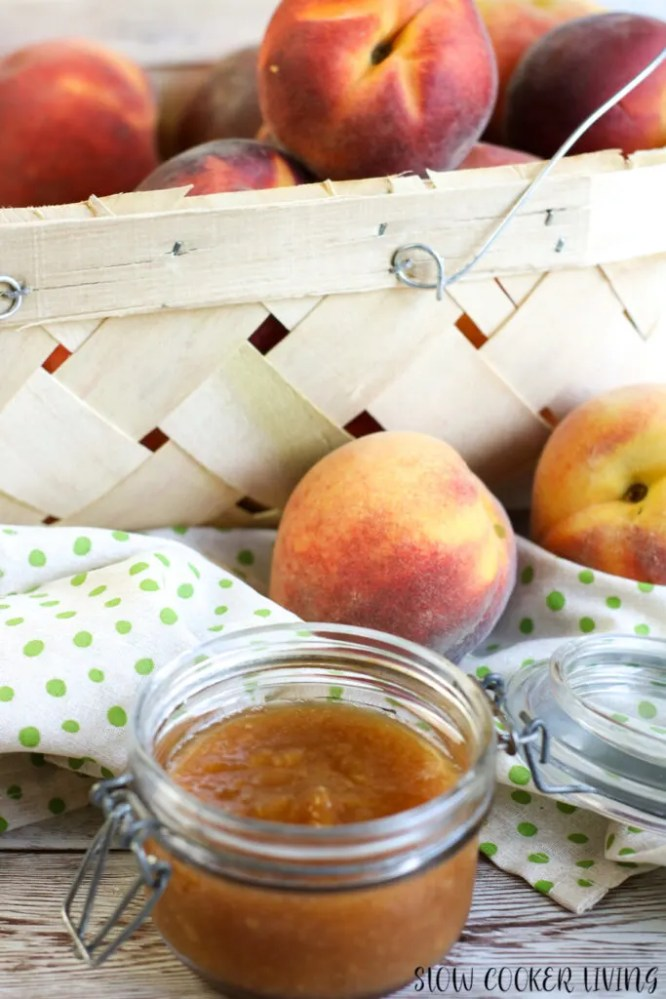 Another view of the finished peach butter recipe in front of a basket of peaches.