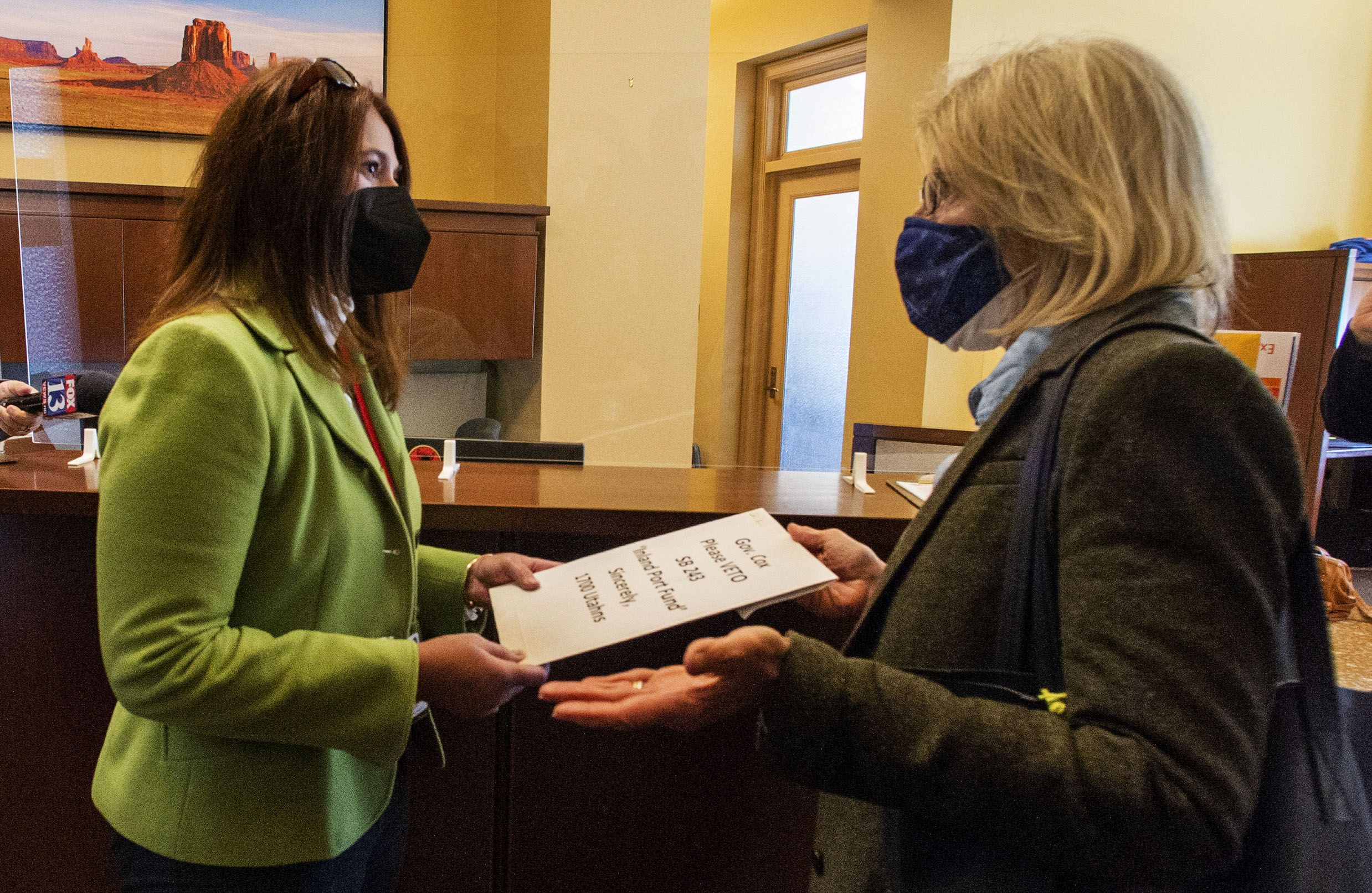 (Rick Egan | The Salt Lake Tribune)   Jennifer Napier-Pearce, senior advisor and director of communications to Utah Gov. Spencer Cox, accepts a letter from Sarah Buck signed by more than 1,700 people, urging Utah Gov. Spencer Cox to veto SB243, at the Capitol on Wednesday, March 17, 2021.