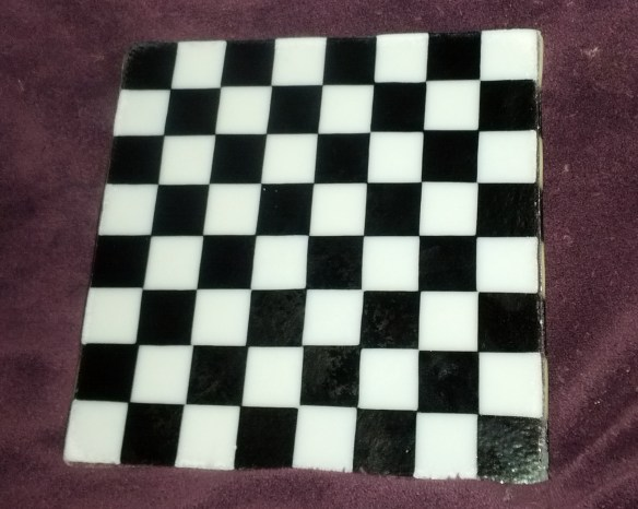 black and white fused glass chessboard laying on a plum purple blanket.