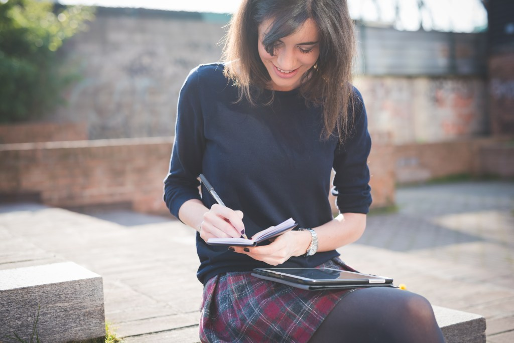 young pretty woman in town using tablet multitasking
