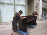 2 movers wheeling a desk on flat dollies, downtown Vancouver